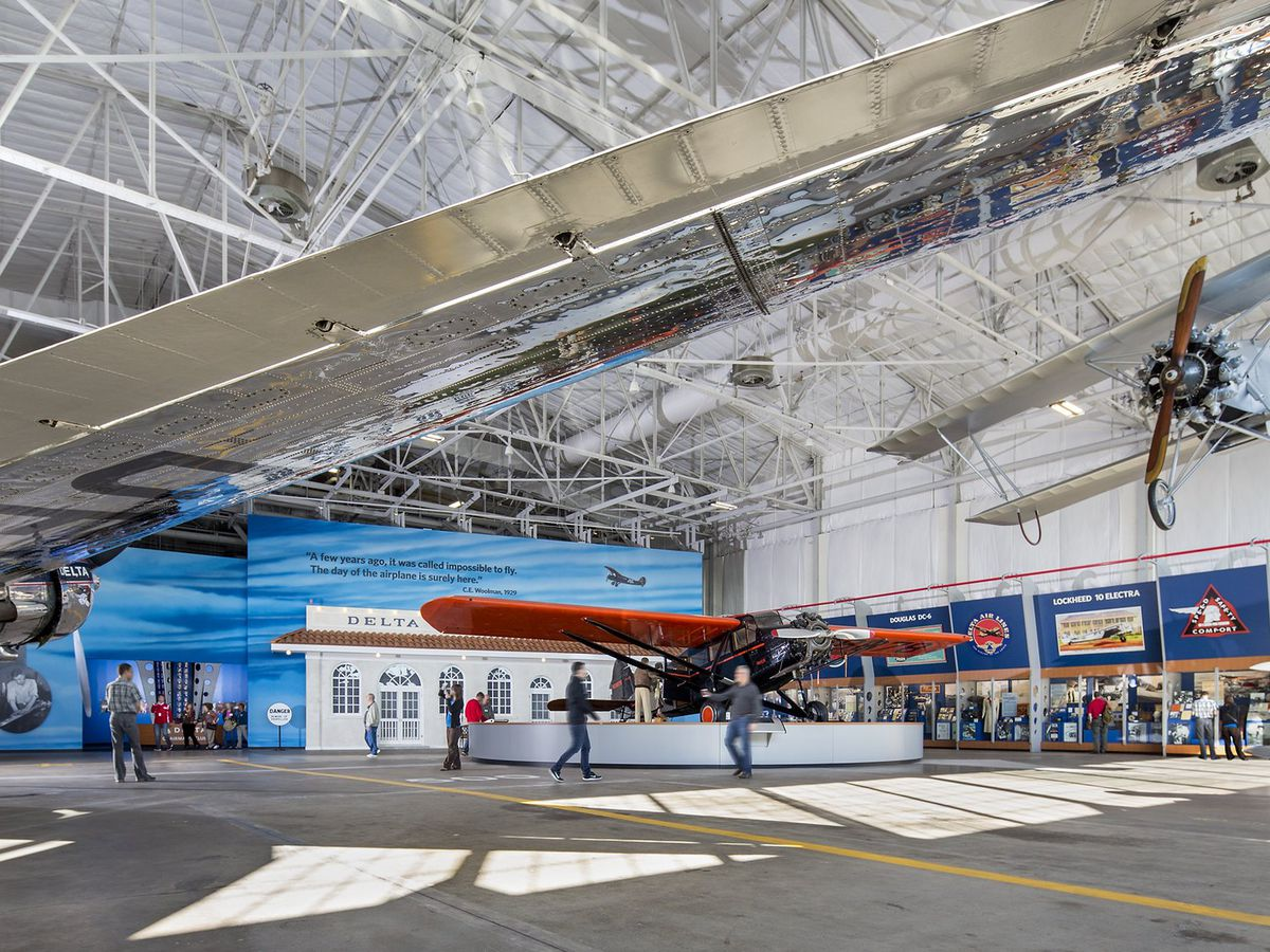 Airport hangar with a biplane hanging from the ceiling.