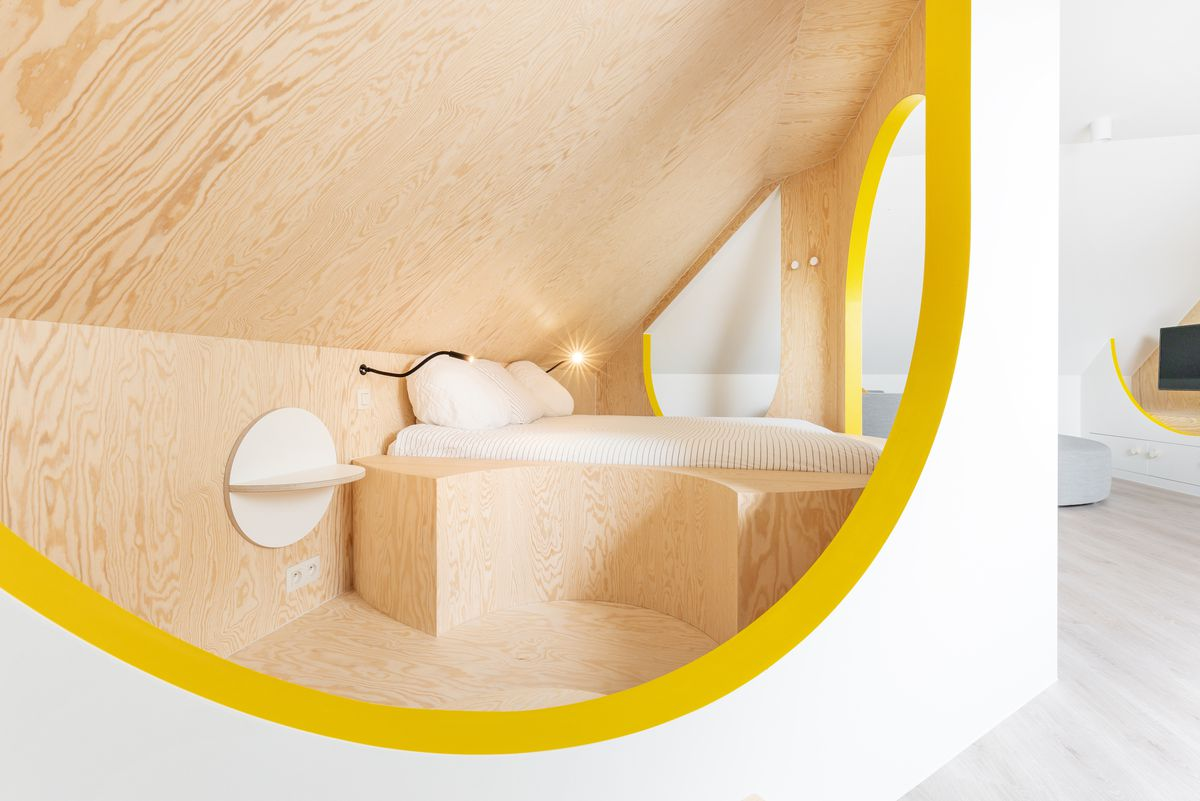 Sleeping area with plywood walls and yellow accent paint.