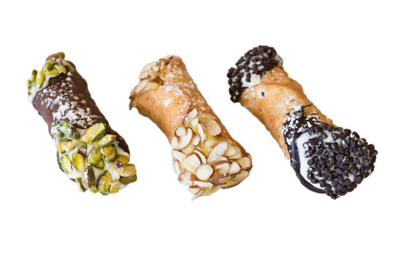 A line of three cannoli from Mike's Pastry and Modern Pastry on a white background. One is chocolate covered and garnished with pistachios, one is garnished with slivered almonds, and the third has chocolate chips.