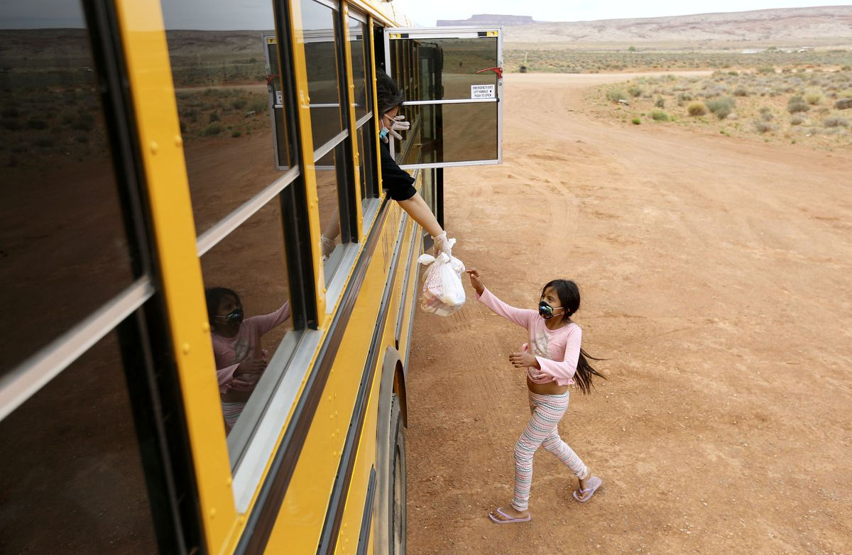 Cara Luna, Tsébii'nidzisgai Elementary School fourth grade teacher, hands a bag of food to Alexus Bedonie from a school bus in Oljato-Monument Valley, San Juan County, on Thursday, April 30, 2020. While schools are closed due to COVID-19, buses are delivering homework and food to students two days a week. Navajo nation has one of the highest per capita COVID-19 infection rates in the country.