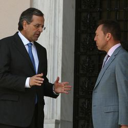 """Greece's Prime Minister Antonis Samaras, left, and Finance Minister Yannis Stournaras talk after a meeting with the heads of the two junior coalition parties at Maximos Mansion in Athens, Thursday, Sept. 27, 2012. Stournaras says the heads of the three parties in the governing coalition have reached a """"basic agreement"""" on an austerity package for 2013-14.The cuts are essential if Greece is to continue receiving funds from international emergency loans."""