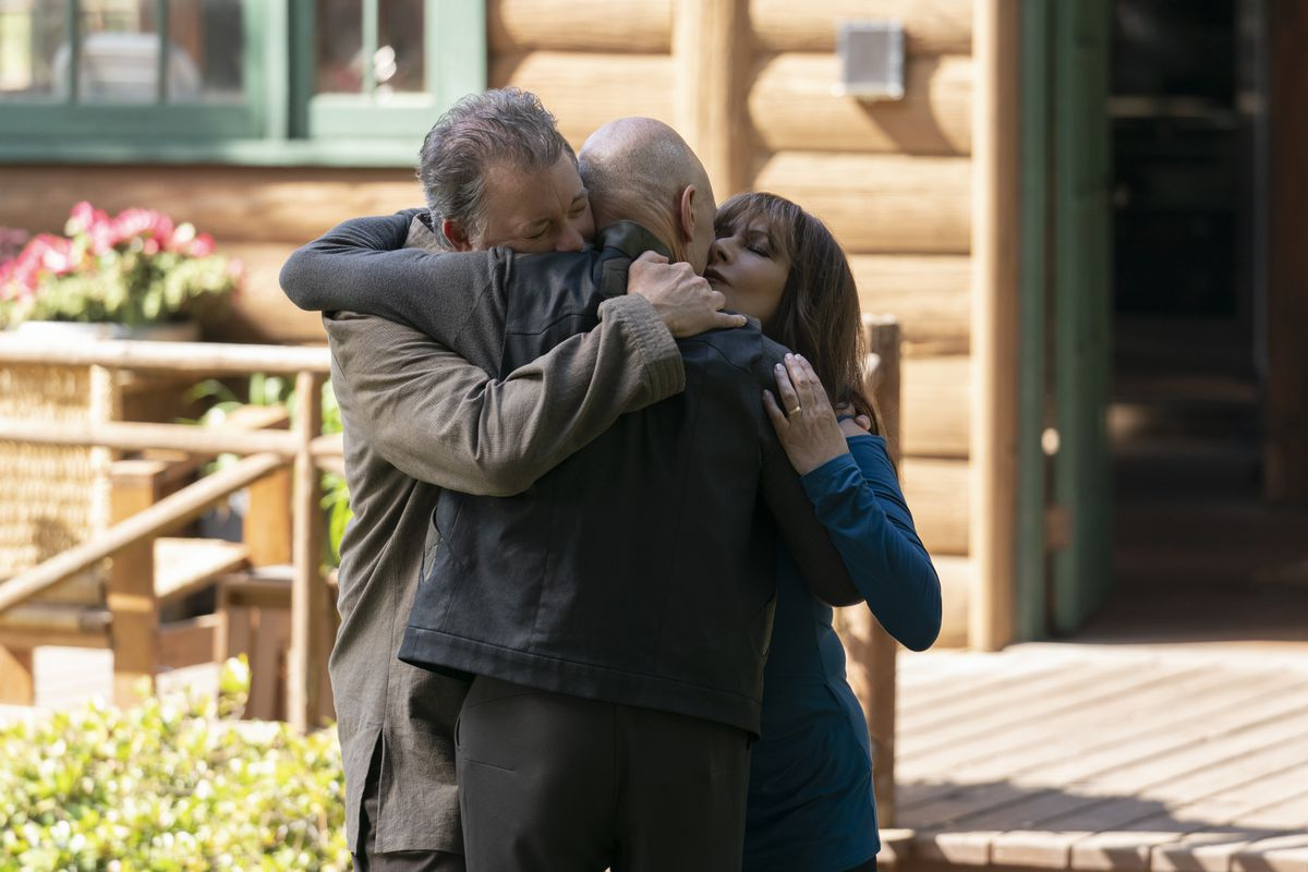 Jonathan Frakes and Marina Sirtis as Riker and Troi hug Patrick Stewart as Picard in front of a fancy sunlit log cabin on Star Trek: Picard.