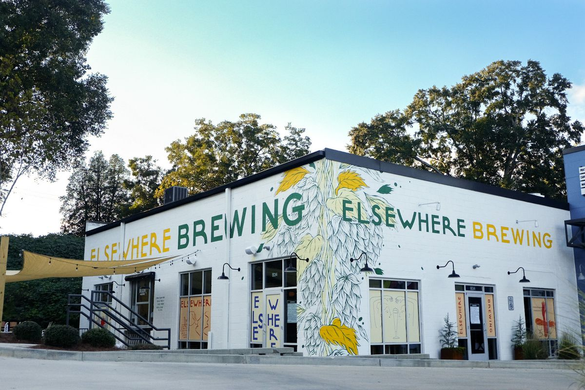 The white-painted brick exterior of Elsewhere Brewing in Grant Park, Atlanta, with hand-painted Elsewhere Brewing logo in green and yellow. A yellow awing is hung over a patio on the side of the building.