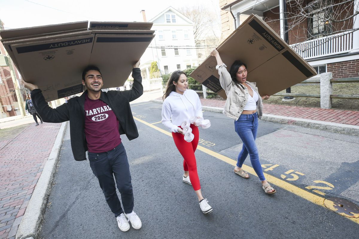 A trio of college students carrying cardboard boxes prepares to pack up their belonging to move out of their dorms at Harvard.