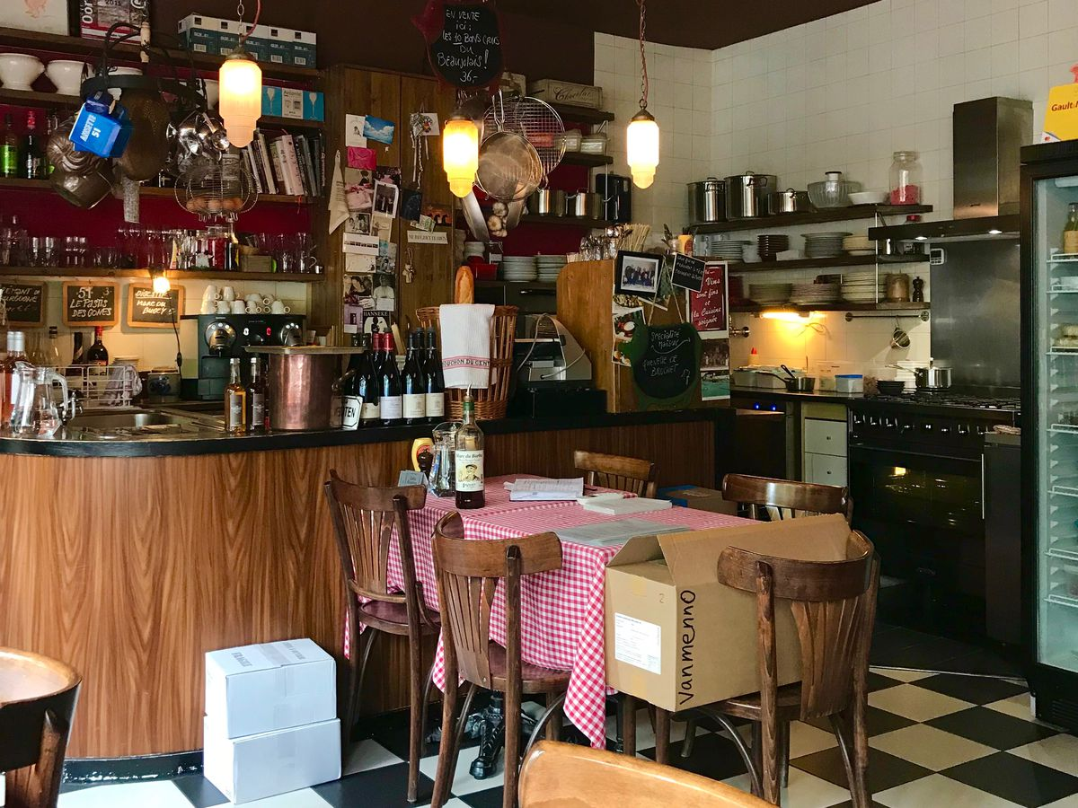 A homey restaurant interior with checkerboard floor tiling, red check tablecloths on small tables, an intimate little cafe bar and soft pendant lights.