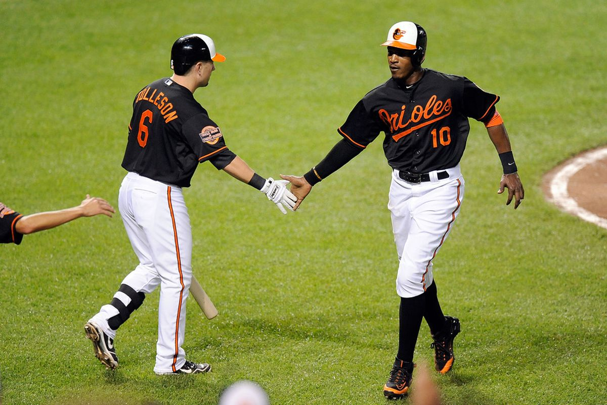 BALTIMORE, MD - MAY 25:  Adam Jones #10 of the Baltimore Orioles celebrates with Steve Tolleson #6 after scoring in the fifth inning against the Kansas City Royals at Oriole Park at Camden Yards.