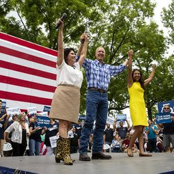 Gov. Bruce Rauner wraps up the Governor's Day program with Lt. Gov. Evelyn Sanguinetti, left, and candidate for attorney general, Erika Harold, Wednesday, Aug. 15, 2018 at the Illinois State Fair in Springfield, Ill. (Rich Saal/The State Journal-Register via AP)