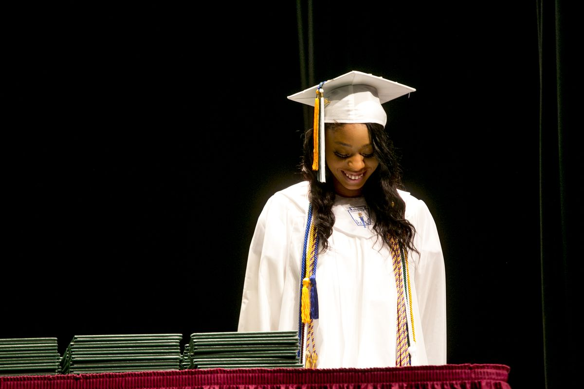 Marqell McClendon, valedictorian of the Cody High School graduating class this year, reacts as a teacher introduces her during the June graduation ceremony.