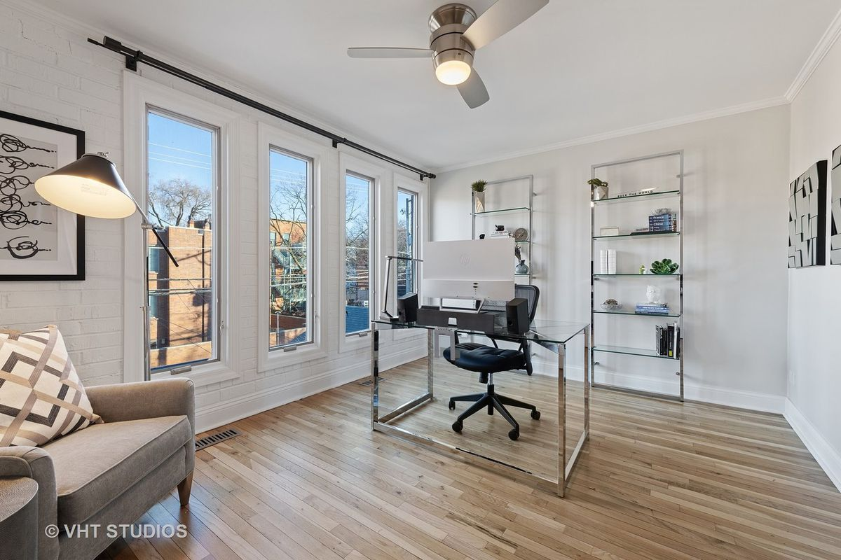 The at home office on the top floor features a modern glass and chrome desk. There are built-in shelves and an upholstered chair.