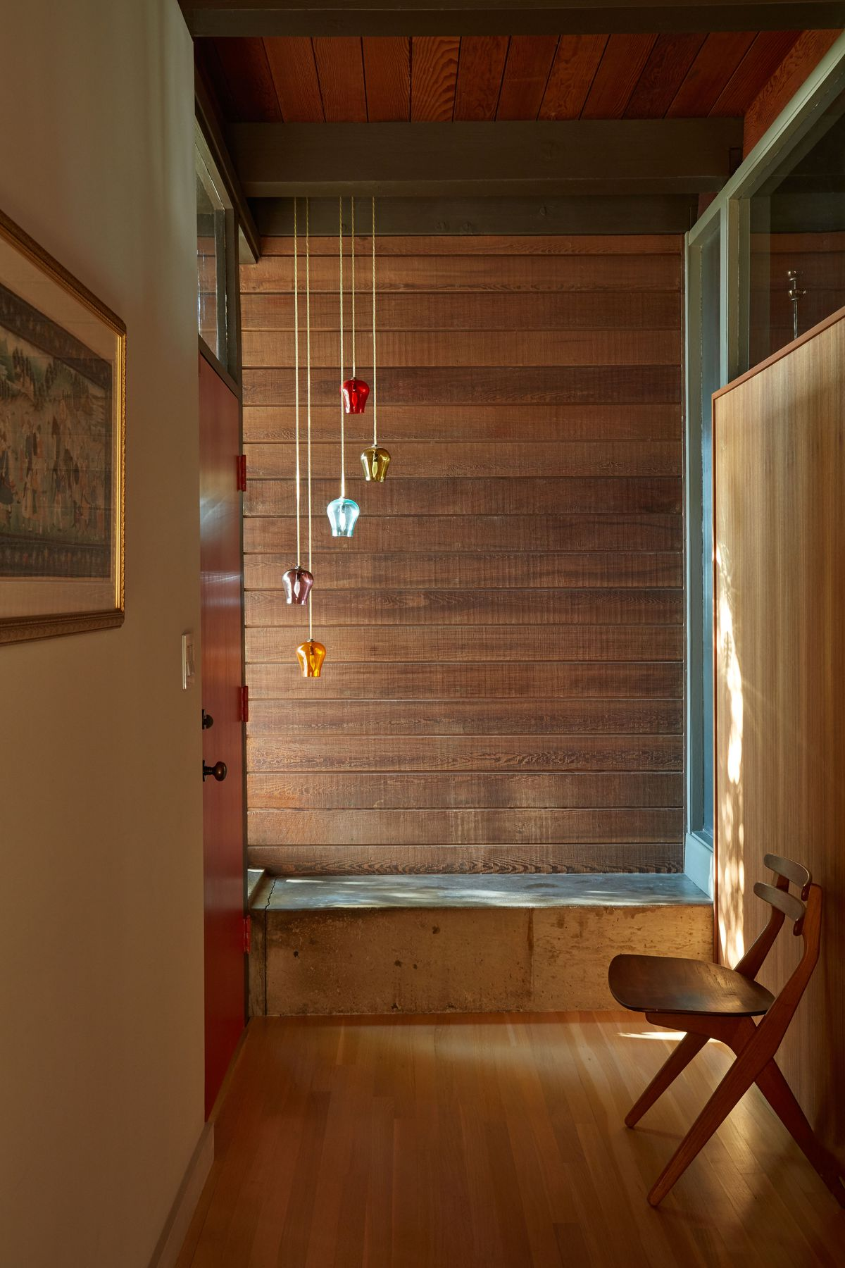 An entryway. The floor is wooden. There are colorful glass objects hanging from strings. A chair sits against a wall.