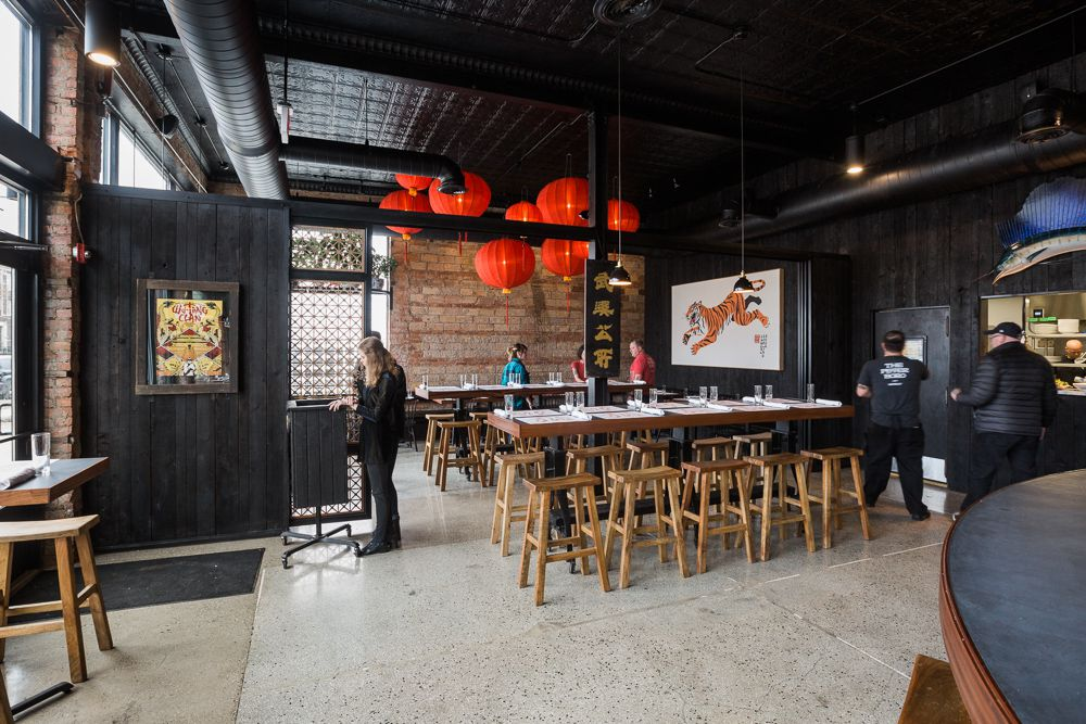 A restaurant dining room full of chairs surrounding two communal tables. Round Chinese lanterns hang from the ceiling.
