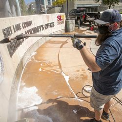 Chad Rasmussen, owner of Royce Industries, uses a pressure washer to clean paint from the sign in front of the Salt Lake County District Attorney's Office building in Salt Lake City on Friday, July 10, 2020. The building suffered tens of thousands of dollars in damage when protesters broke out at least three windows and spread red paint over large portions of the building and area in front of the structure on Thursday.