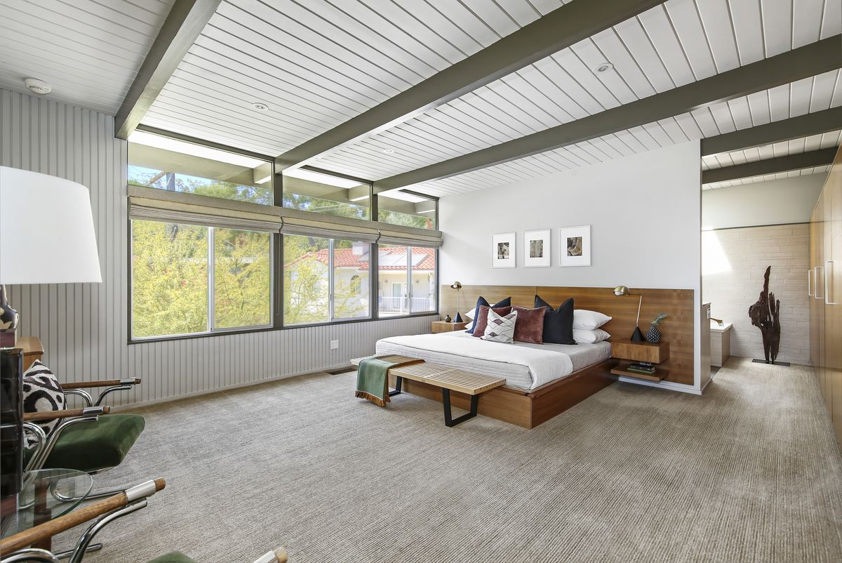 Large room with built-in wooden platform bed, large windows, and olive green beams in the ceilings.