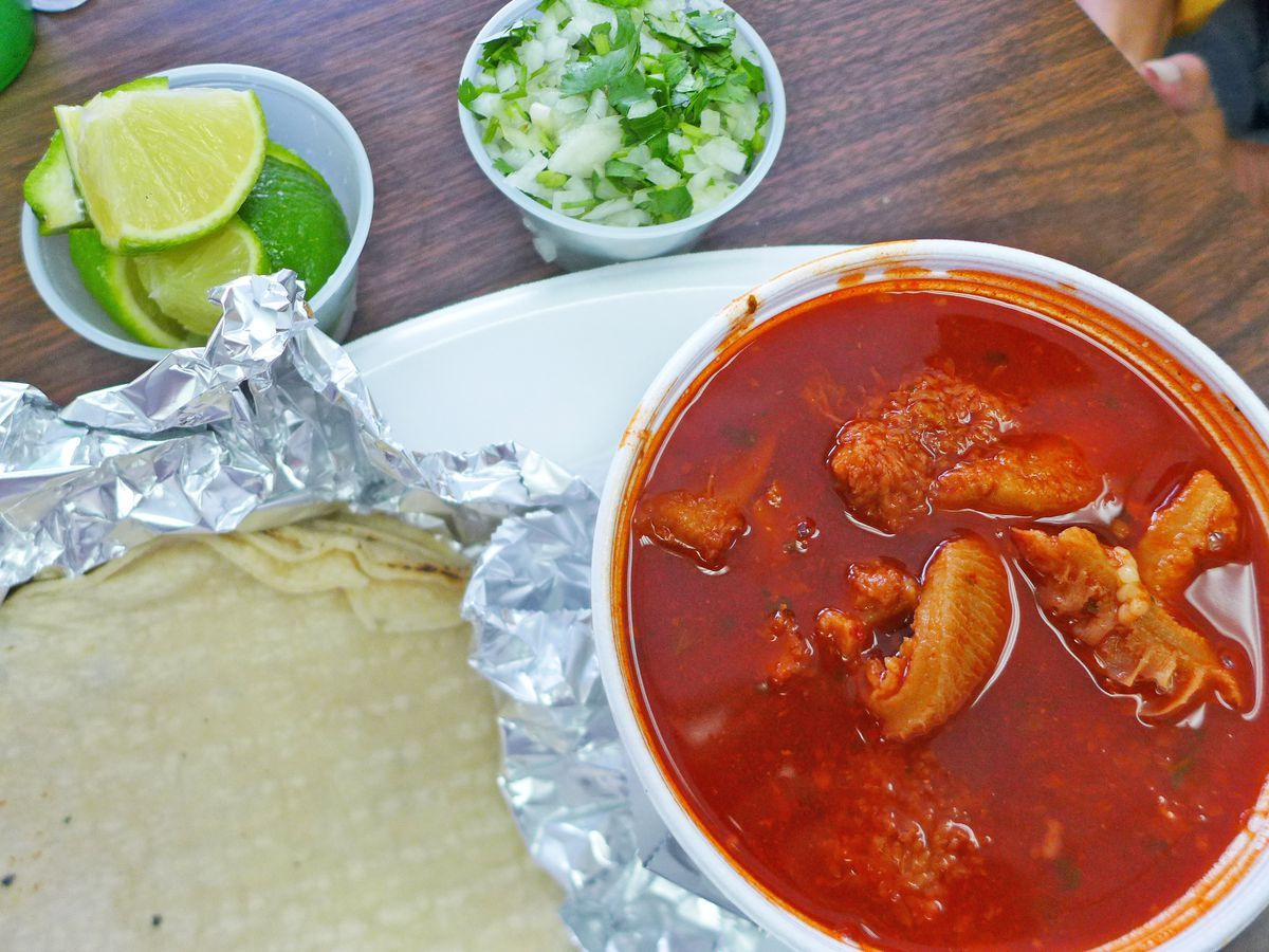 A red tripe soup served with tortillas, lime wedges, and fresh herbs.