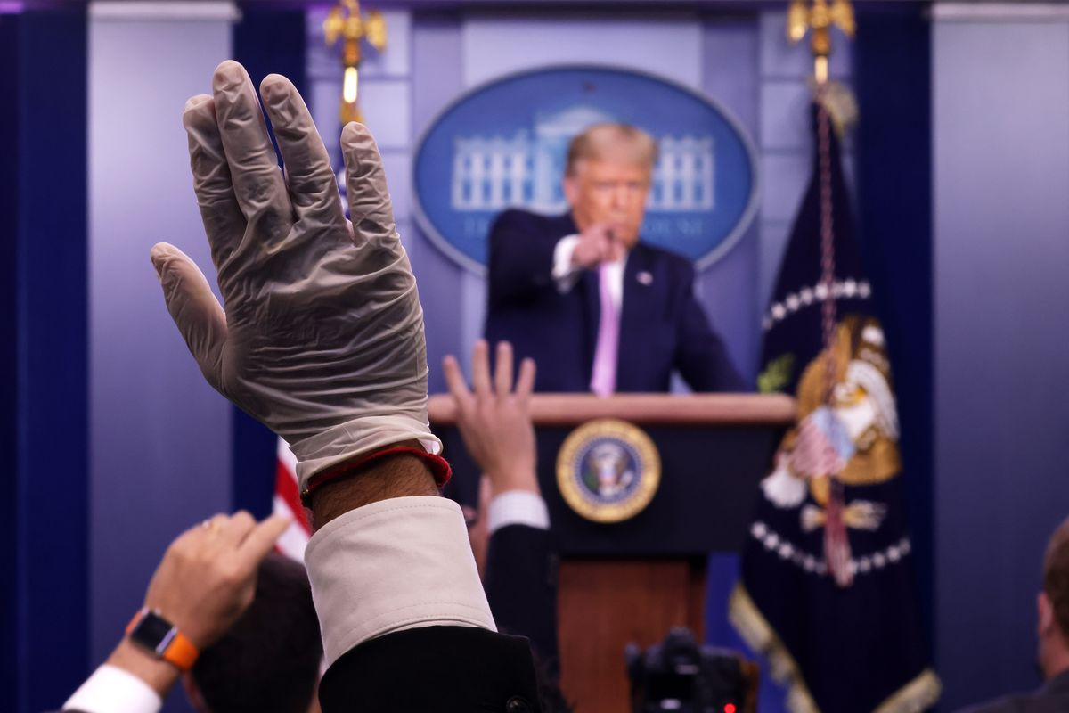 A reporter's hand wearing a plastic glove is raised at a press briefing at the White House. President Trump points to a reporter from behind the podium.