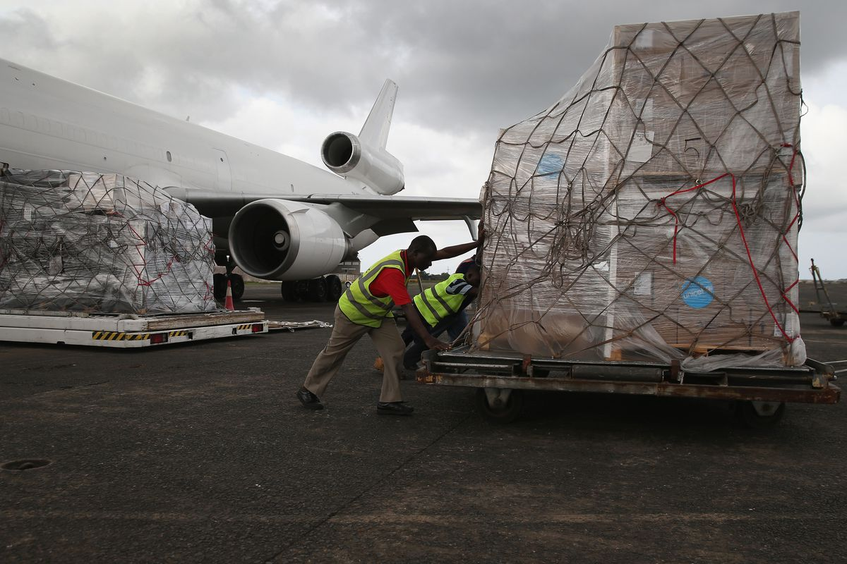 Workers unload Ebola relief aid from a cargo flight organized by the United Nations Children's Fund in Harbel, Liberia.