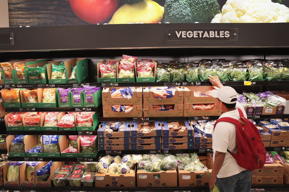 A grocery store produce section with meal kits on the shelves