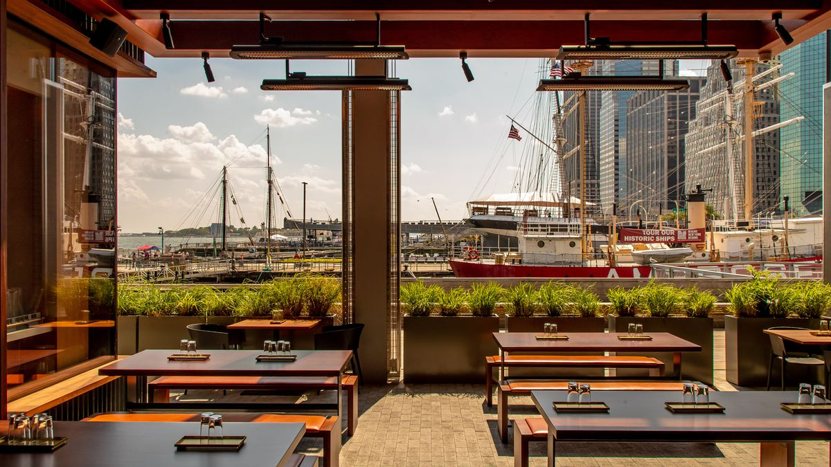 Patio seating at Bar Wayo has a view of boats in the water