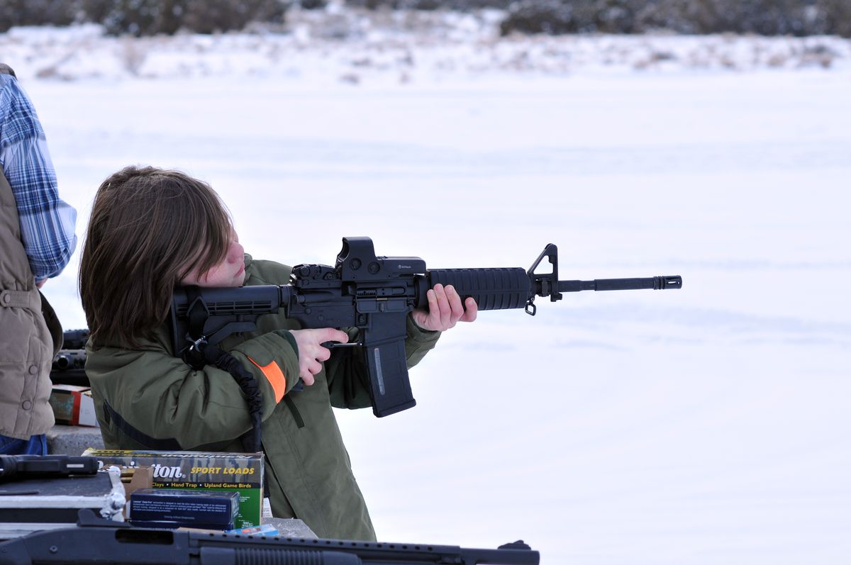 A young boy fires an AR-15 at a shooting range.