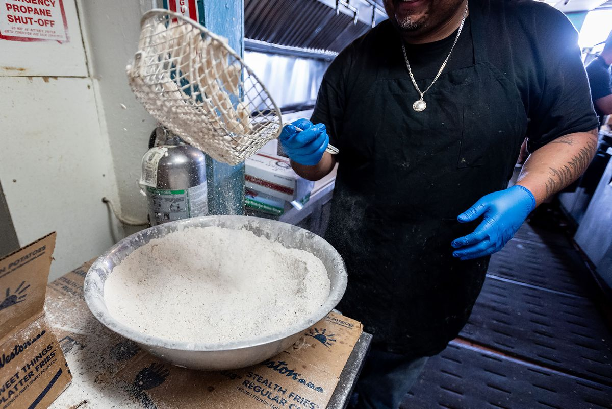 A man sifts fried fish into a bowl.