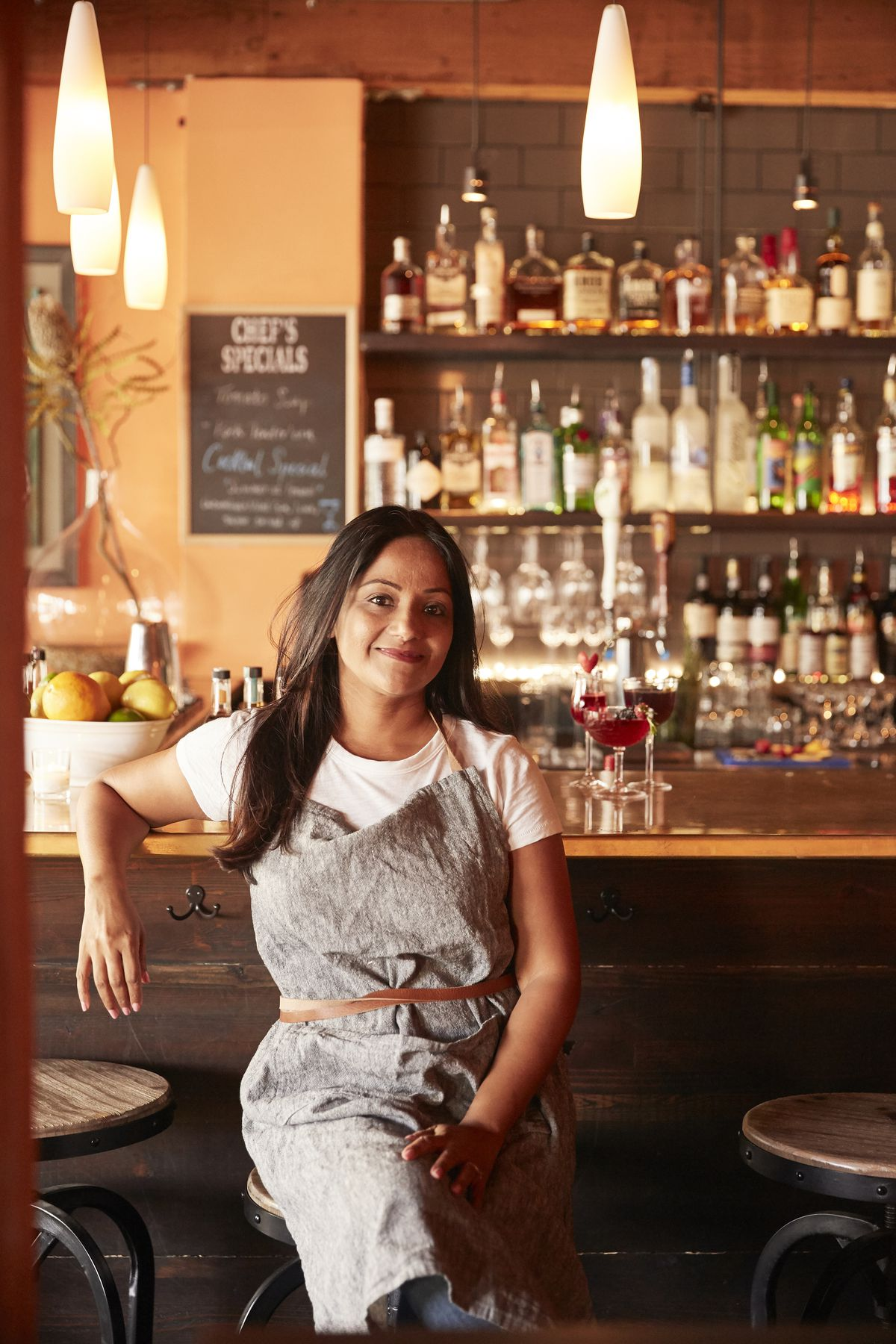 A photo of chef Preeti Agarwal in front of the bar at Pomerol.