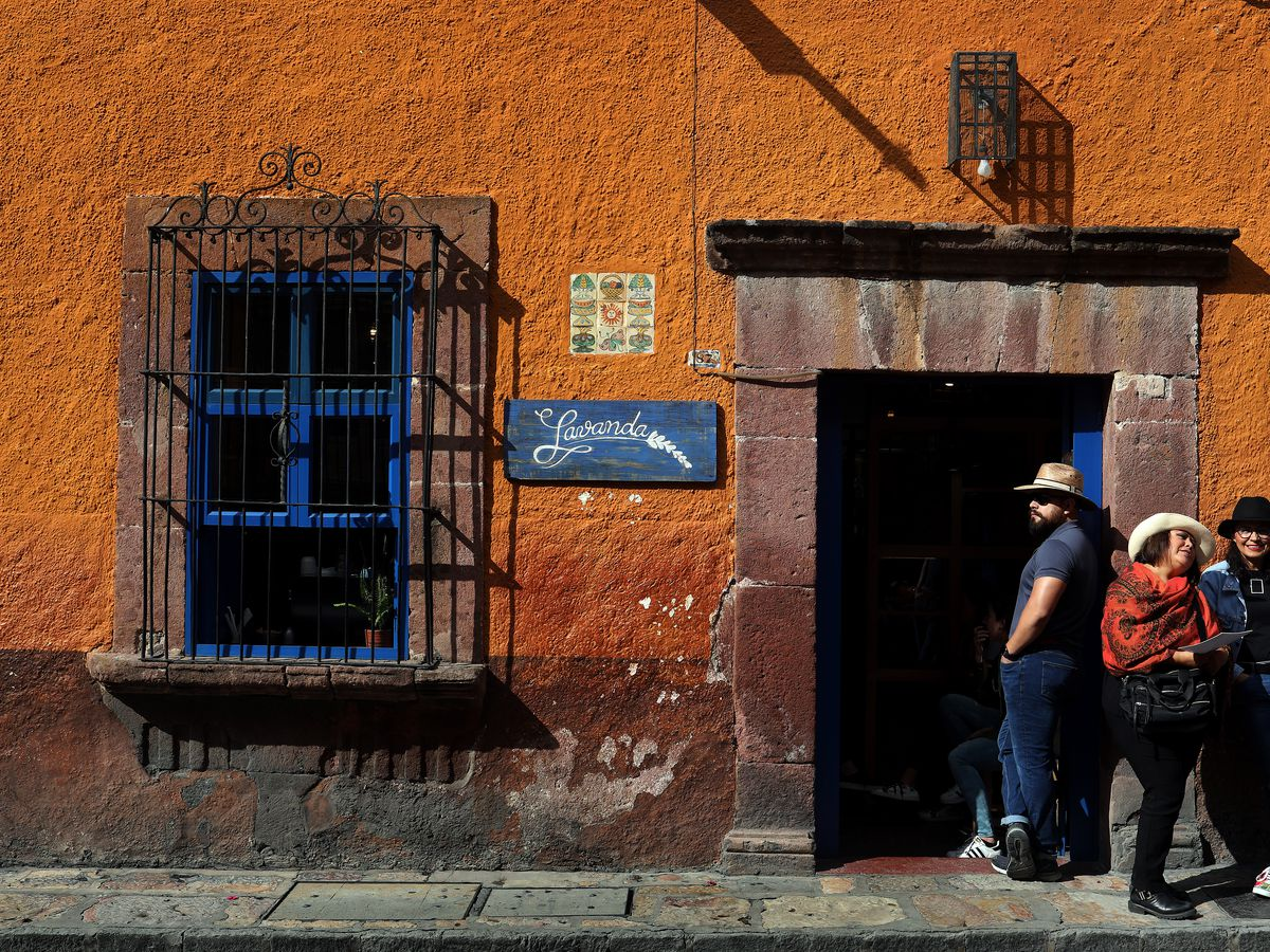 People in cowboy hats stand outside an orange building.