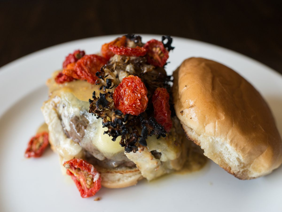 An Elk burger sits on a white plate at Bukowski Tavern, with the top bun askew to show off the tomato and mushroom topping