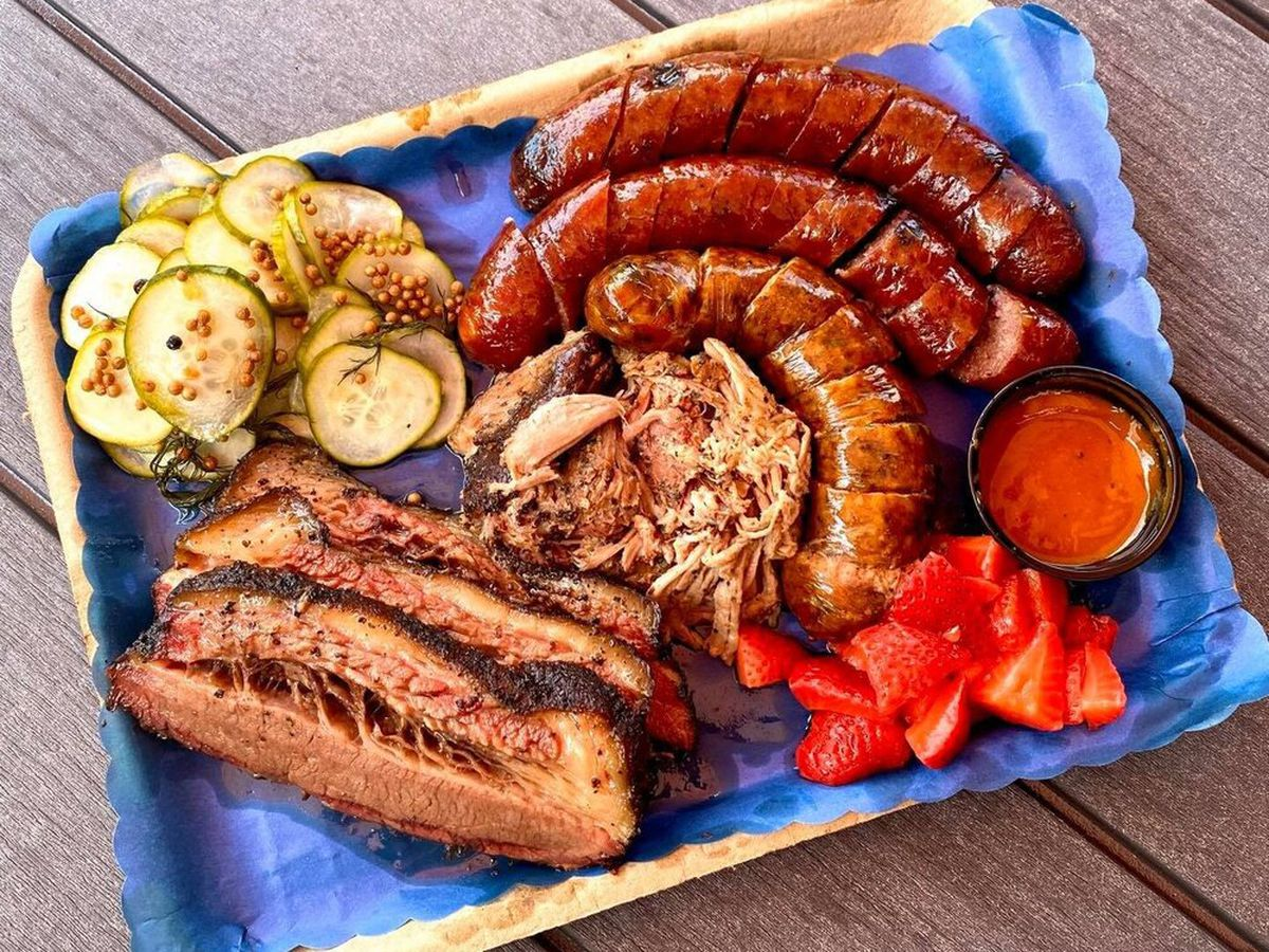 A lined paper tray with thick slices of brisket, three sliced sausages, pickles, strawberries, and sauce, on a wooden table