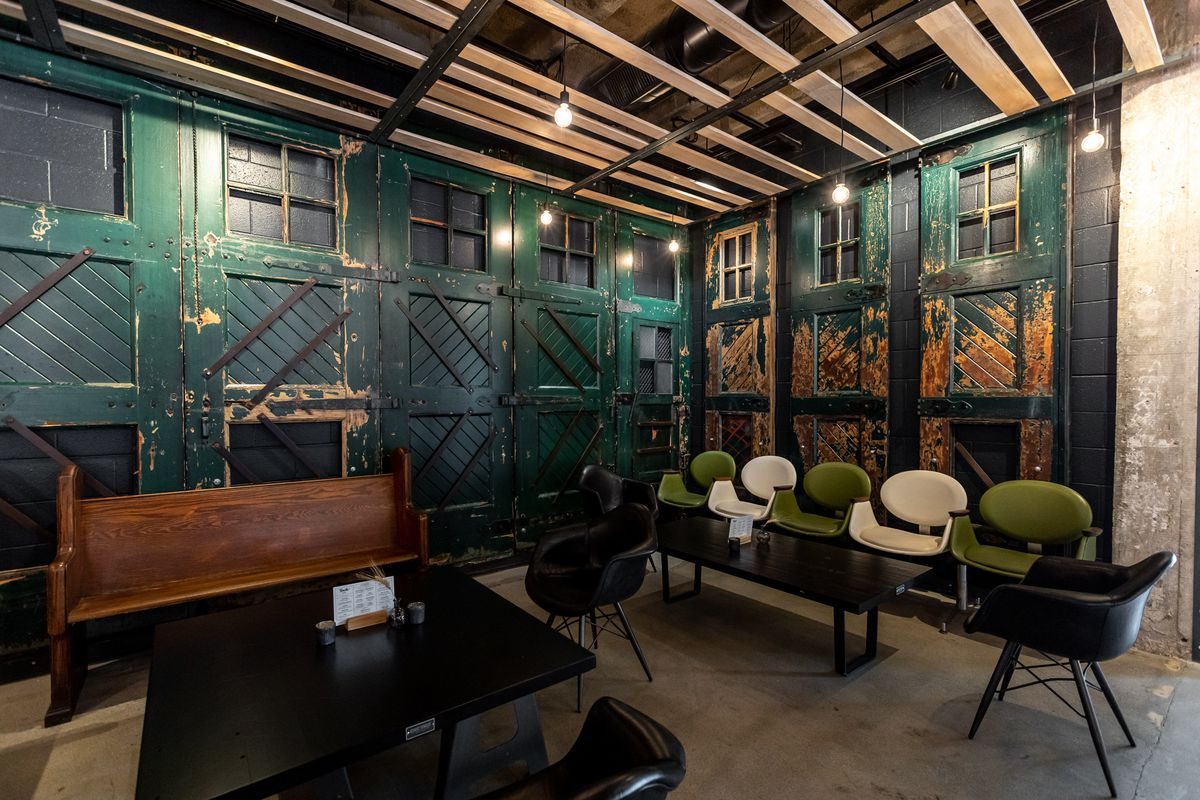 Green antique doors hang in a lounge area at Smith & Co with white, green, and black chairs, a two black coffee tables, and a wooden pew.