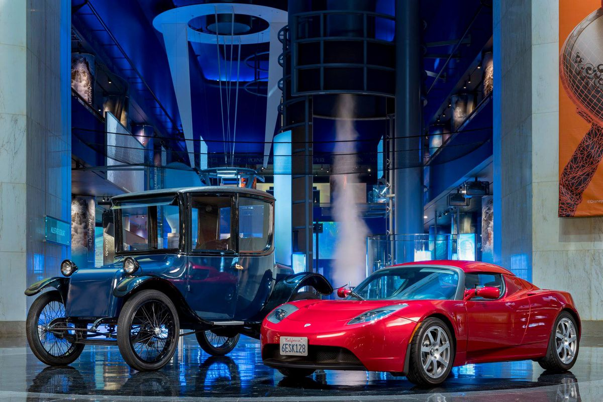 An old 1923 Milburn Electric beside a modern Tesla Roadster.   J.B. Spector/Museum of Science and Industry.
