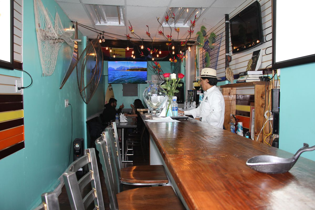A long wooden bar counter with tall wooden chairs placed against it. A man can be seen standing in the distance at the bar.