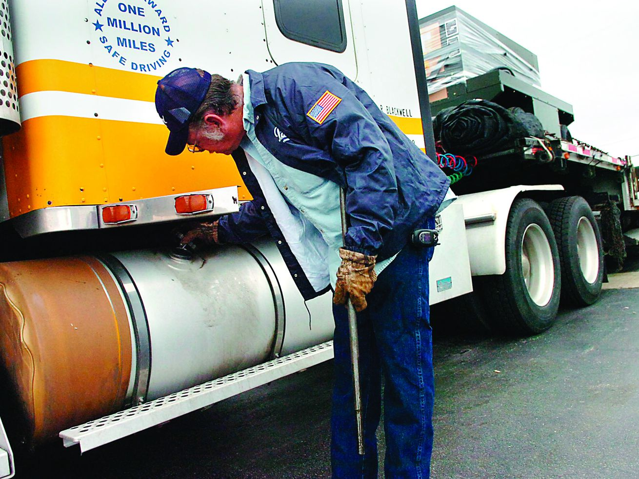 A driver checks the gas level in one of two 150-gallon tanks on his diesel semi-truck in this file photo from 2008.