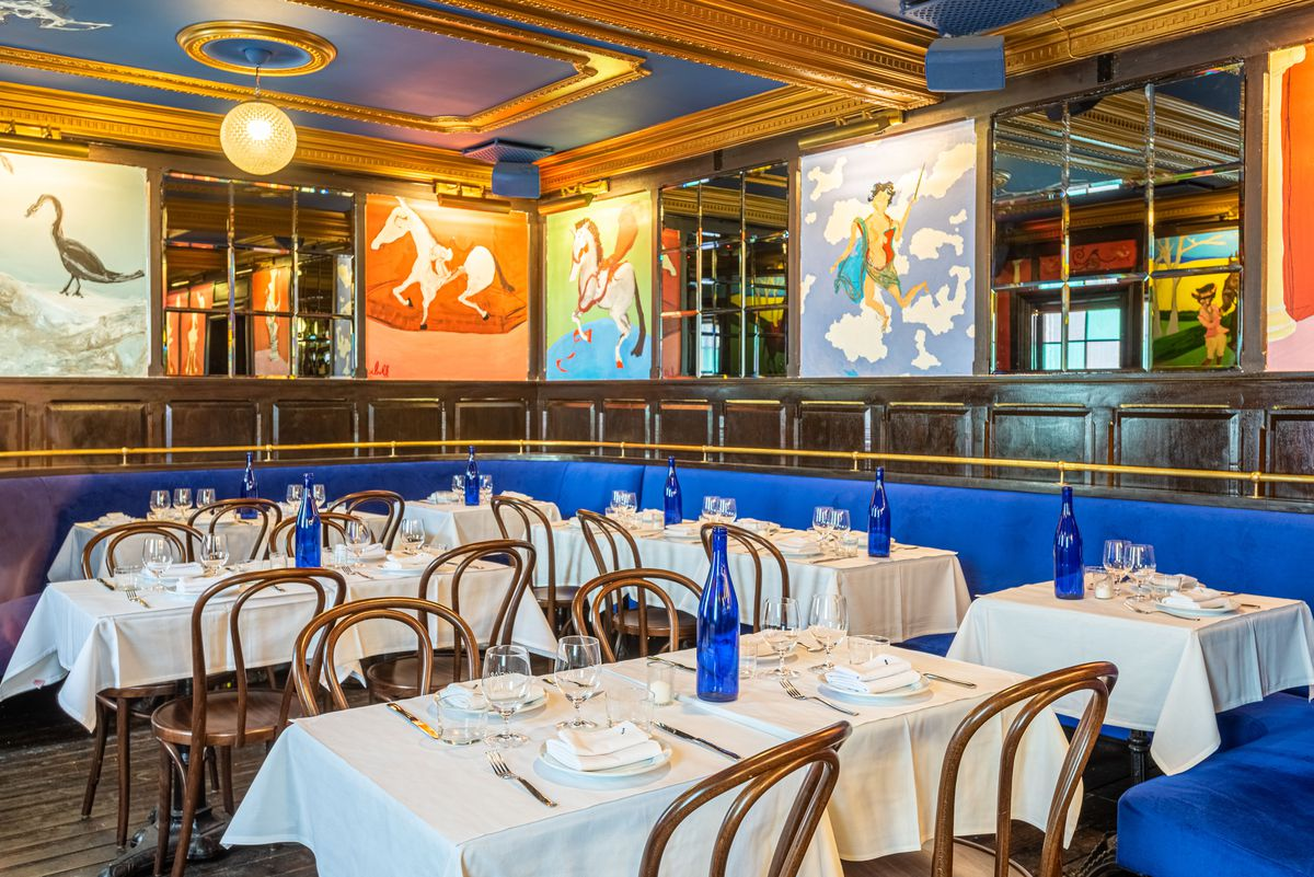 A maximal, colorful dining room with gold gilding and lots of blue and painted horses.