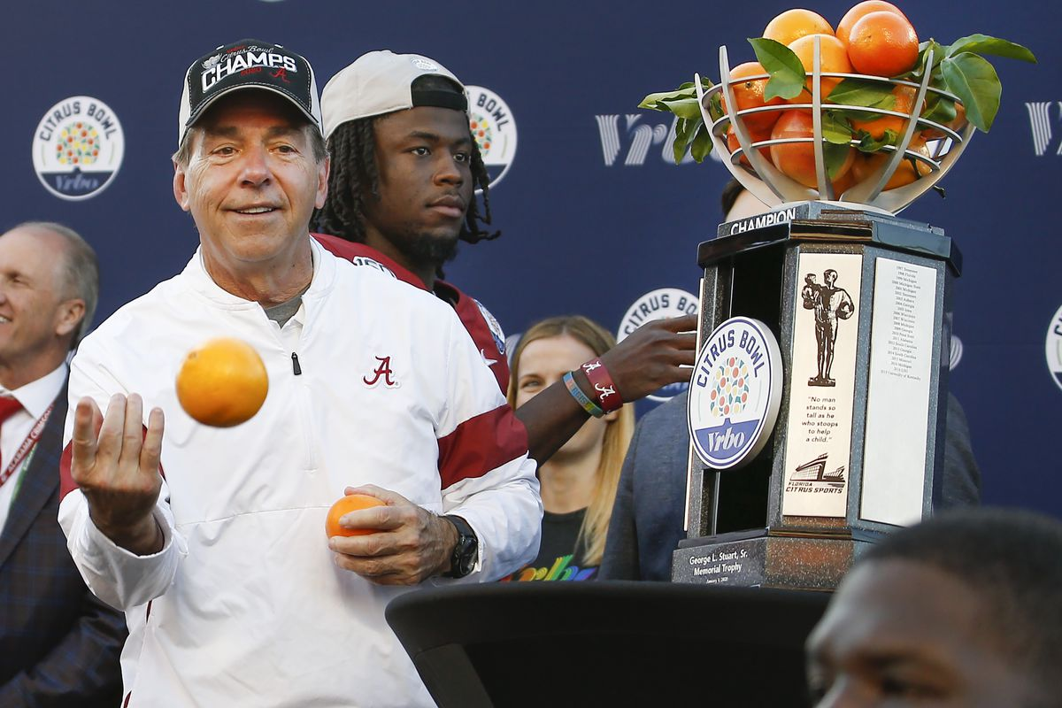 Jan 1, 2020; Orlando, Florida, USA; Alabama Crimson Tide head coach Nick Saban tosses oranges to his players from the Champions trophy after defeating the Michigan Wolverines the 2020 VRBO Citrus Bowl at Camping World Stadium.
