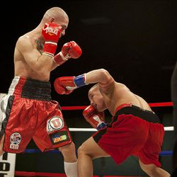 """Allen Litzau, right, evades a blow from Chris """"KidKayo"""" Fernandez during their boxing match at the South Towne Expo Center. Fernandez won the bout after four rounds, Saturday, Dec. 15, 2012."""