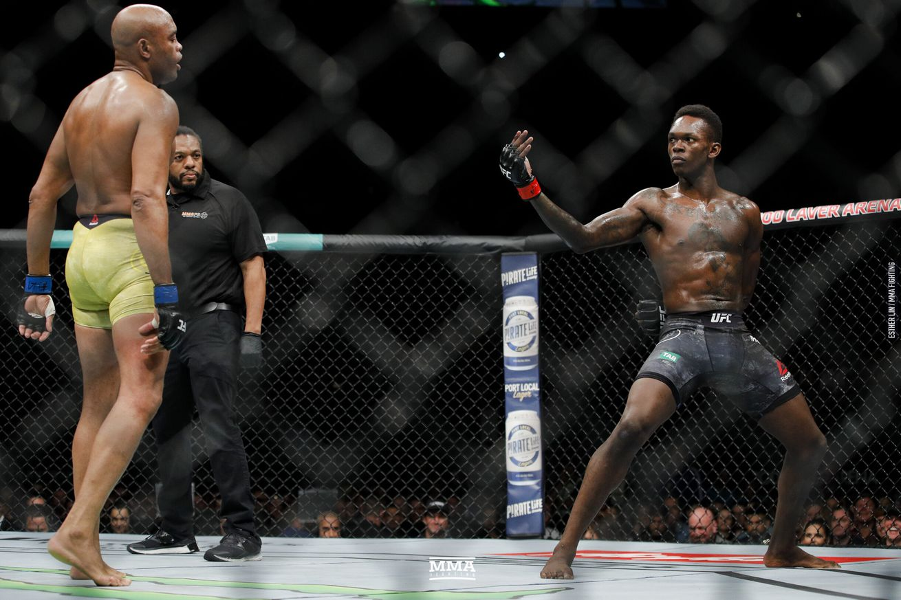 Israel Adesanya (right) strikes a pose during his UFC 234 fight with Anderson Silva (left)