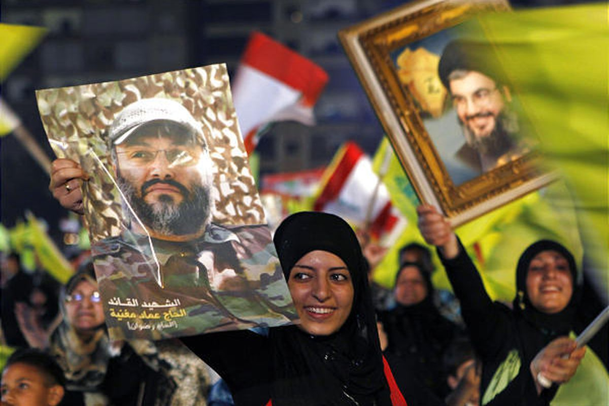 Hezbollah supporters hold posters of slain leader Imad Mughniyeh and leader Sheik Hassan Nasrallah.
