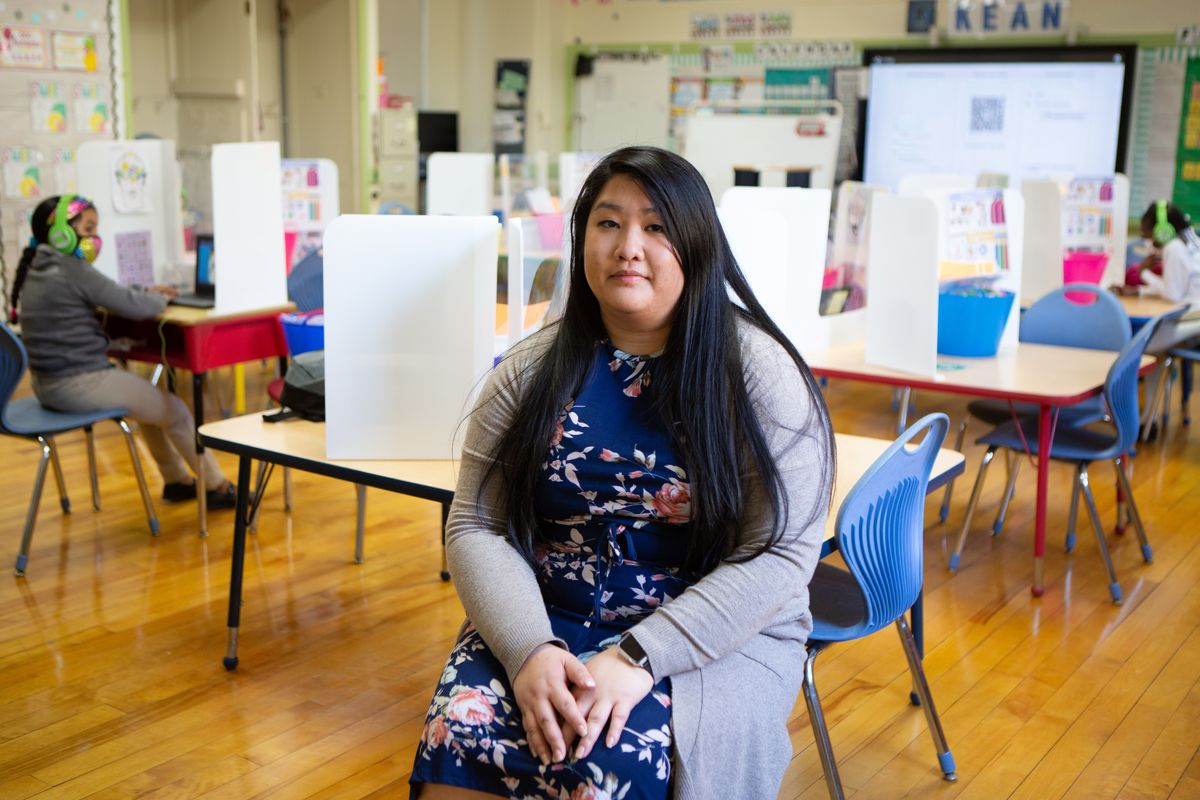 First grade teacher Molisa Cheng, wearing a blue floral-patterned dress and grey sweater, poses for a portrait in her classroom.