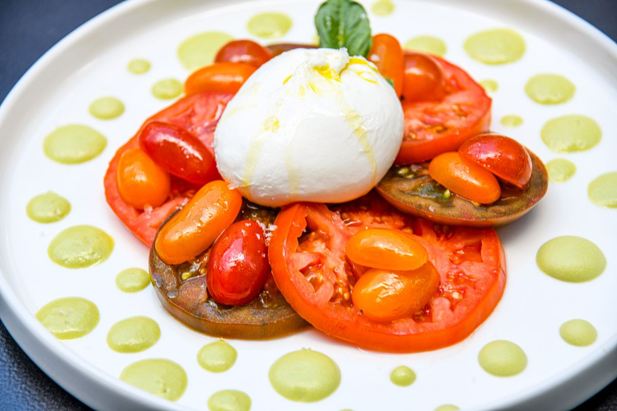 Caprese salad with a dollop of burrata on top and a fresh, green basil leaf.