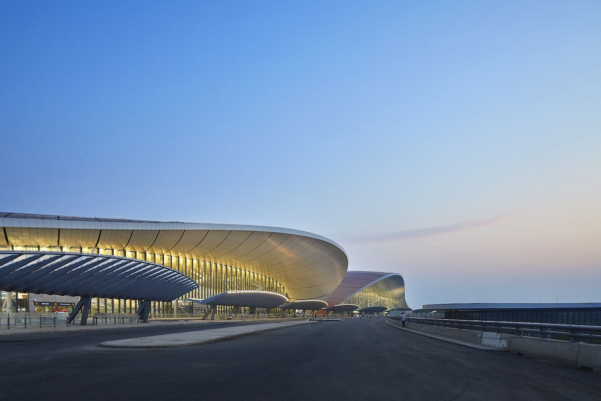 Outside of airport with curving roofline at sunrise.