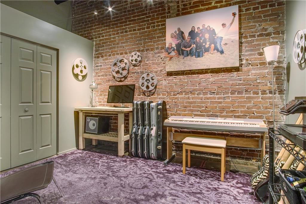 A bedroom with a brick wall and much recording equipment.