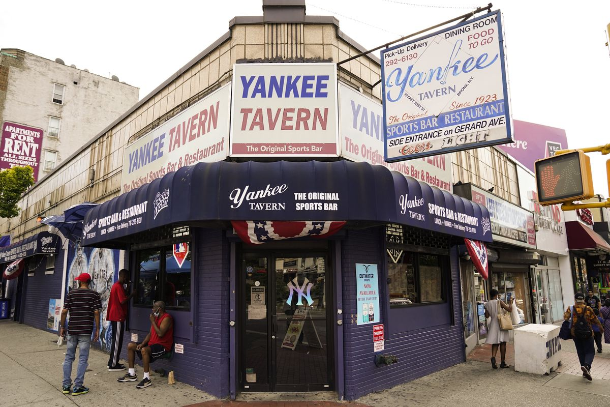 Pedestrians pass the Yankee Tavern, which has been in business since 1927 but has taken a huge financial hit from the coronavirus pandemic.