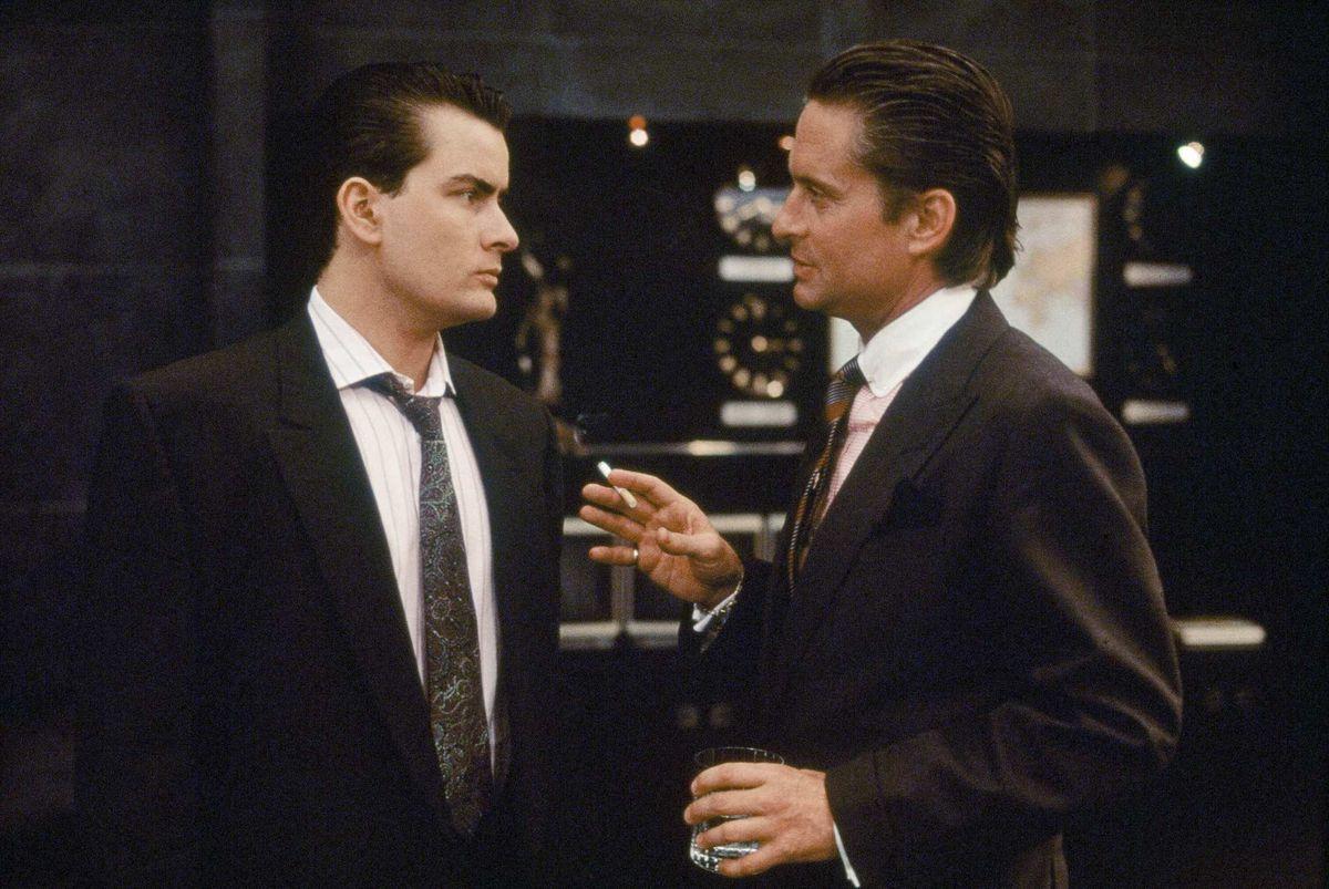 "Charlie Sheen as Bud Fox and Michael Douglas as Gordon ""Greed Is Good"" Gekko in Wall Street."