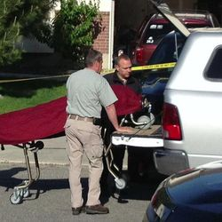 Medical examiner officials remove the second body of one of the victims as other law enforcement officials from Davis County investigate the deaths of two young boys Thursday, May 23, 2013, in West Point.