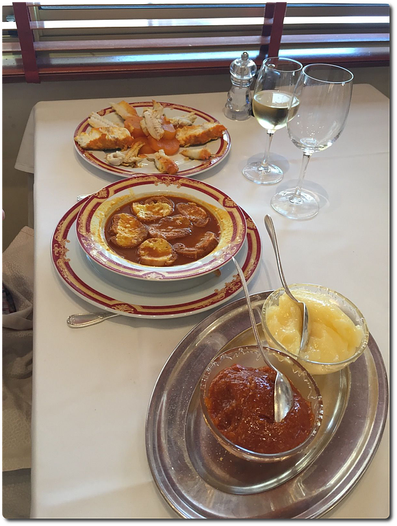 A soup dish filled with bouillabaisse sits in the middle of a table between a dish of cooked fish and shellfish, and a serving dish with two bowls of condiments, as well as wine glasses in front of a window with the blinds down letting in peaks of light