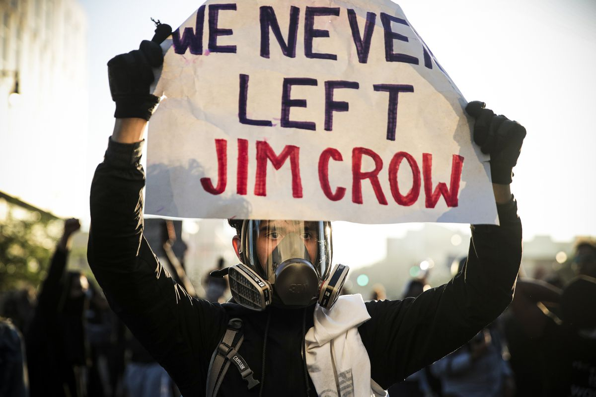 "A man in a full face mask with a ventilator over his mouth holds a blue and red sign, ""We never let Jim Crow."""