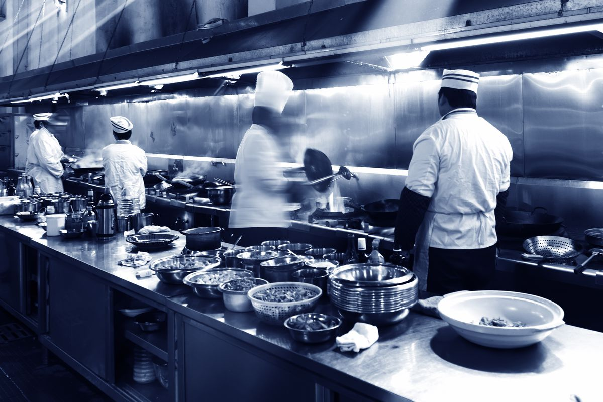 Four chefs work on the line inside a restaurant kitchen, as plates stack up on a nearby counter.