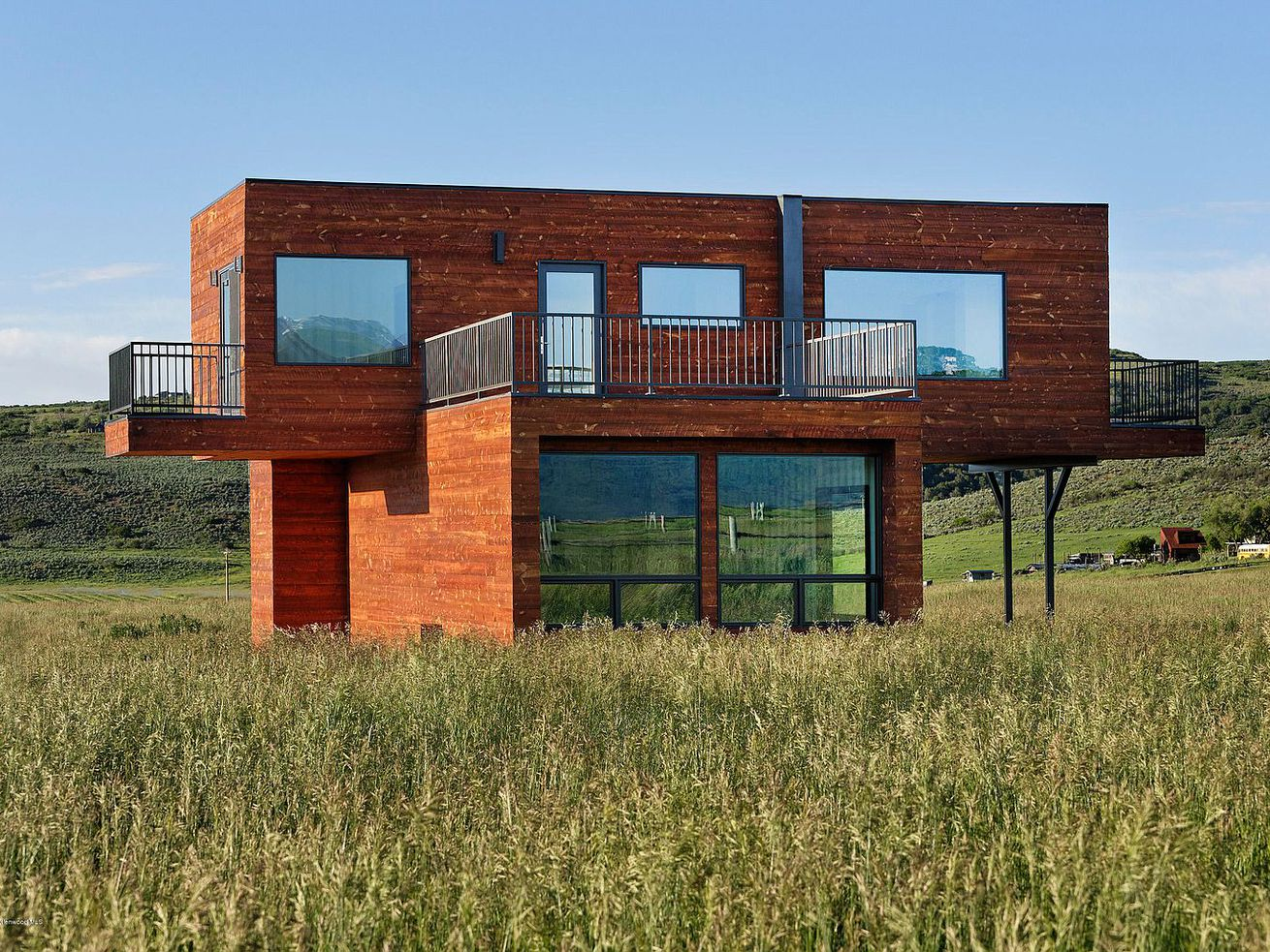 Wood-covered container home on grassy land.