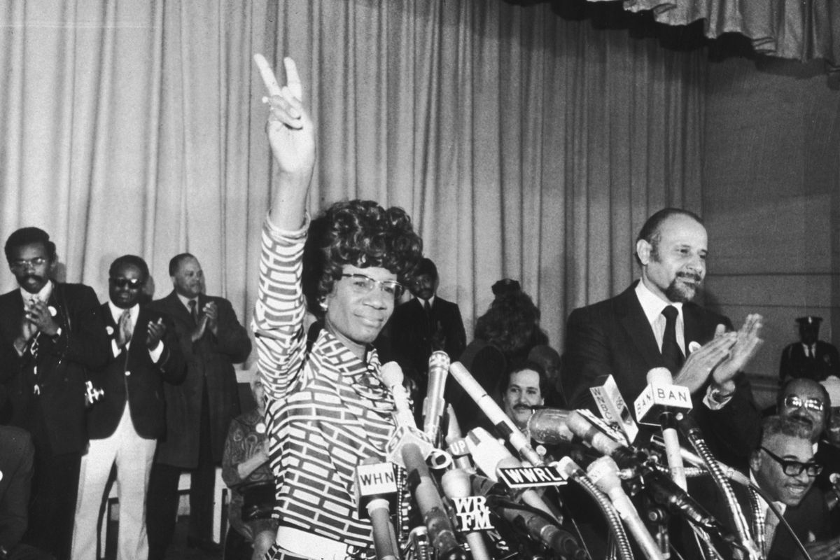 Shirley Chisholm in 1972 standing behind a bank of microphones and holding up her hand in a peace sign.