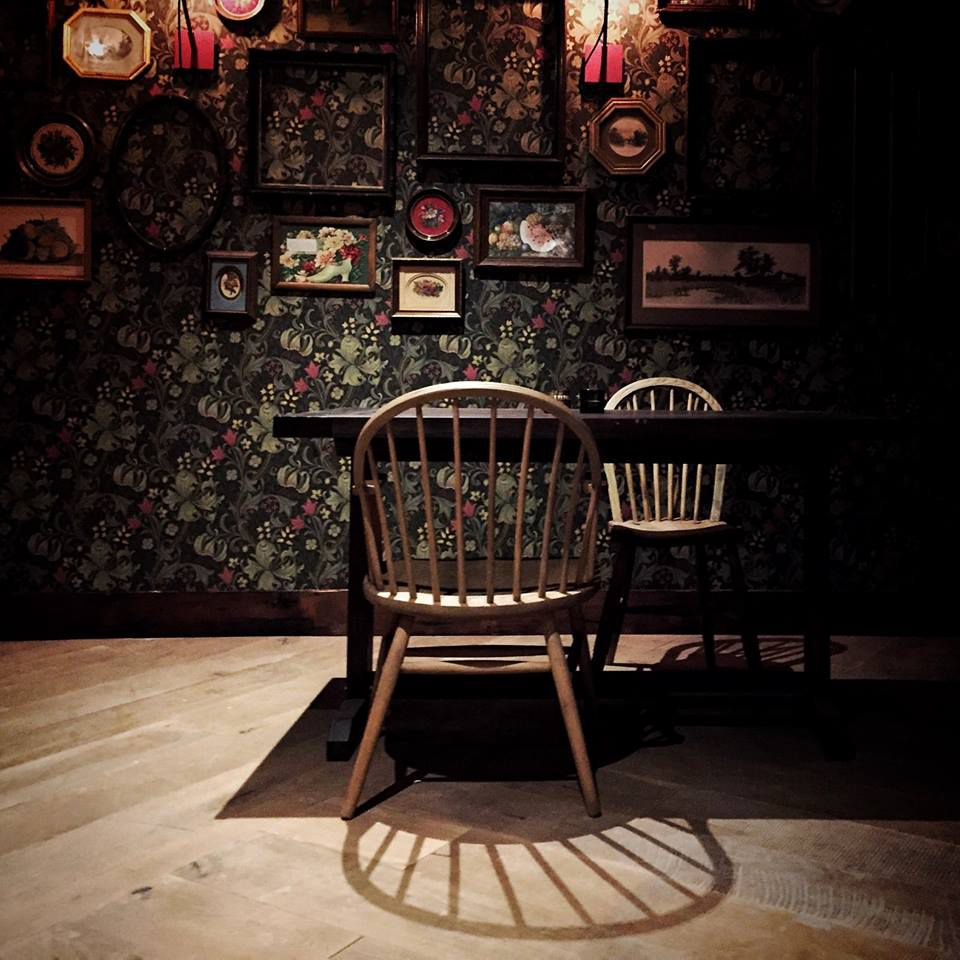 A dimly lit room with black wallpaper decorated with small vintage framed art. A table with a wide backed wooden chair is set against the wall.